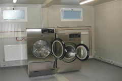 Laundry equipment for a working camp. Fitted into a prefabricated structure. Washing machine 16 kg capacity and dryer.